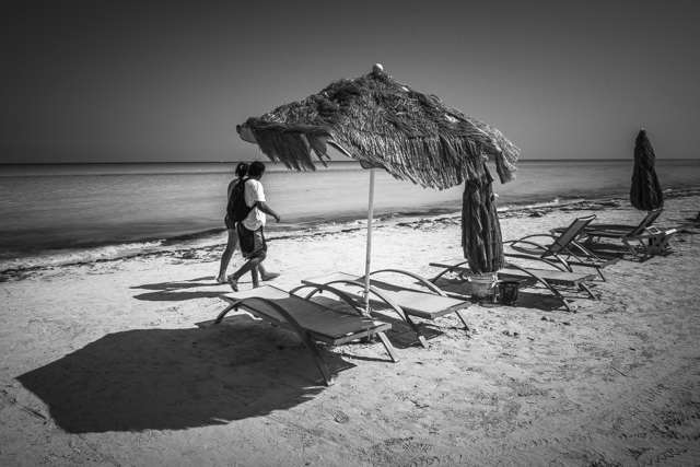 Couple walking and chaise-longue in a beach in Isla Holbox, Quintana Roo (Mexico)