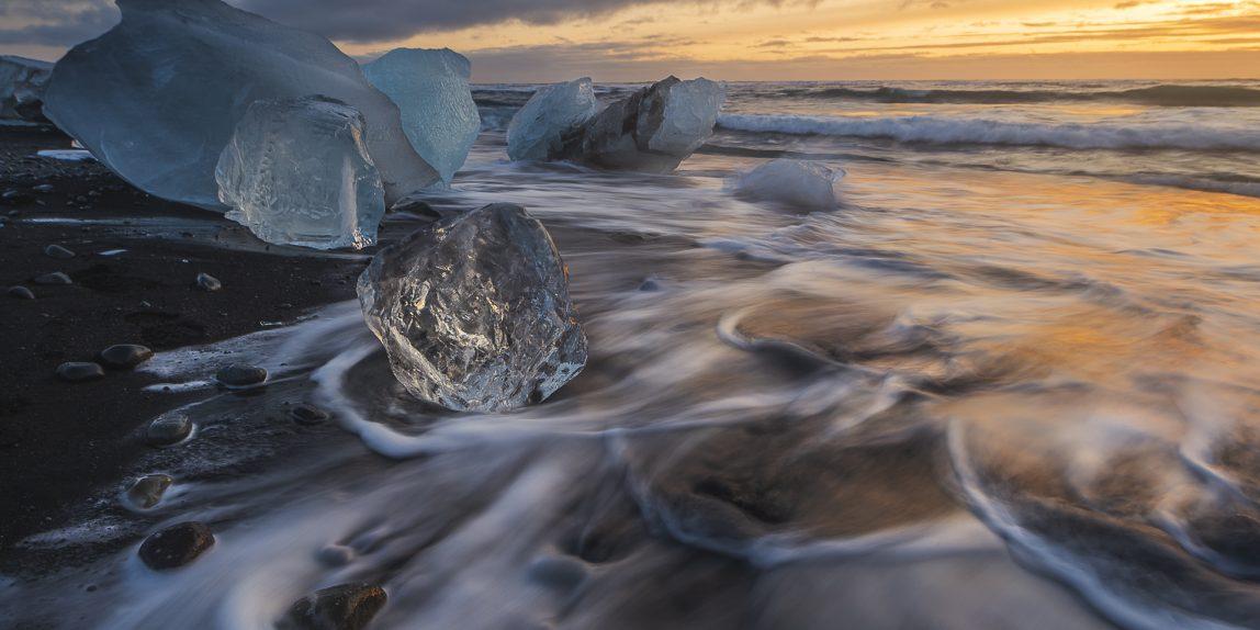 Broken ice from washed up Icebergs on Jokulsarlon black beach at sunset Jokulsarlon South east Iceland